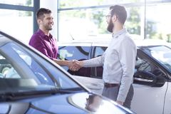 Happy buyer of new car shaking hands with dealer after transaction in the salon. Concept photo royalty free stock photos
