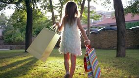 Happy buying, child enjoy new purchases after visiting fashion shop and waving shopping bags in park. Lit by sun rays stock footage
