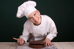 Happy Cake Leveling. Close up capture of a smiling female Pastry Chef leveling a layer of chocolate devil's food cake using a large cake spatula Stock Photography