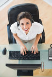Happy call center agent typing while on a call. In her workplace Royalty Free Stock Photography