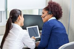 Happy Call Center Employees Discussing While Using stock photo