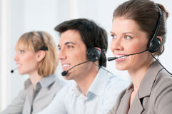 Happy call center operators. Smiling beautiful lady working at call center with colleagues in office Stock Photos
