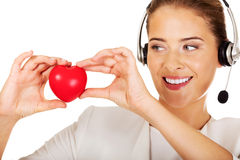 Happy call center woman with heart toy Royalty Free Stock Images