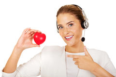 Happy call center woman with heart toy Royalty Free Stock Photography