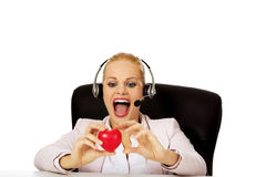 Happy call center woman sitting behind the desk and holding heart model Stock Image