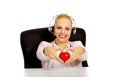 Happy call center woman sitting behind the desk and holding heart model Royalty Free Stock Image