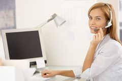 Happy call center worker girl with headset Royalty Free Stock Image