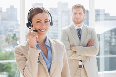 Happy call centre agent with colleague behind her. Happy call centre agent with colleague standing behind her in office Royalty Free Stock Images
