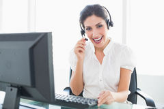 Happy call centre agent sitting at her desk on a call. In her office Royalty Free Stock Photo