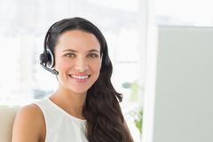 Happy call centre agent sitting at her desk Royalty Free Stock Photography