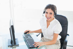 Happy call centre agent working on computer while on a call Stock Photos