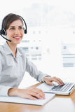Happy call centre agent working at desk. With headset and laptop Royalty Free Stock Photography