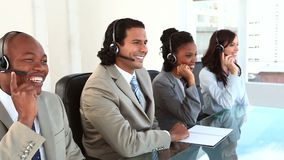 Happy call centre agents working with headsets Royalty Free Stock Photo