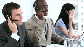 Happy call centre agents working together with headsets Stock Image