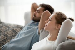 Happy calm couple enjoying relaxation having nap on sofa breathing. Relaxed couple resting on comfortable couch, happy calm men and women enjoying relaxation stock images