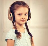 Happy calm kid girl in blue dress listening the music in wireles Royalty Free Stock Photo