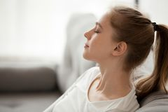 Happy calm woman relaxing breathing fresh air dreaming on couch stock image