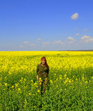 Smiling woman enjoying spring yellow fields Royalty Free Stock Photography