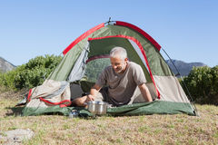 Happy camper cooking on camping stove outside his tent Stock Image