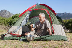 Happy camper holding mug outside his tent Royalty Free Stock Photography