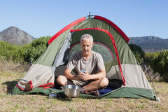 Happy camper holding mug outside his tent Stock Photography