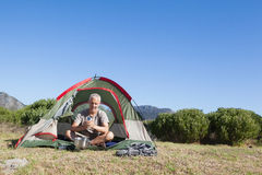 Happy camper holding mug outside his tent Stock Image