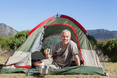 Happy camper holding mug outside his tent Royalty Free Stock Photo