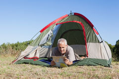 Happy camper looking at map lying in his tent Stock Image