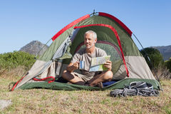 Happy camper looking at map sitting in his tent Royalty Free Stock Photos