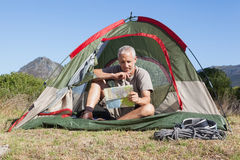 Happy camper looking at map sitting in his tent Royalty Free Stock Photo