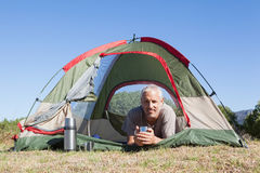 Happy camper smiling at camera lying in his tent Royalty Free Stock Image