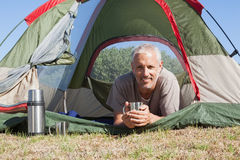 Happy camper smiling at camera lying in his tent Royalty Free Stock Photography