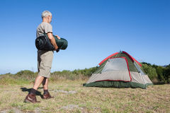 Happy camper walking towards his tent holding sleeping bag Royalty Free Stock Photo