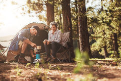 Happy campers making coffee in the wilderness stock photography