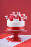Happy Canada Day celebration cake. With flags, marshmallow and candy decorations on a red cake stand on a white table against a red  background Stock Photos