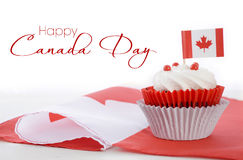 Happy Canada Day Cupcake. Happy Canada Day celebration cupcake with red and white Canadian maple leaf flag on white wood table, and sample text Stock Photo