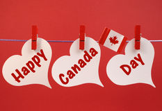 Happy Canada Day message greeting with the Canadian maple leaf flag hanging from pegs on a line. Against a red background, for July 1 holiday Stock Images