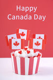 Happy Canada Day Party Cupcakes. Happy Canada Day Party Cupcake with maple leaf flags on a white wood table against a red background Stock Image
