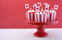 Happy Canada Day Party Cupcakes. On a red cake stand with maple leaf flags on a white wood table and red background Royalty Free Stock Photos