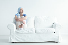 Happy cancer patient. Feeling relieved and holding her knees on a white sofa stock photos