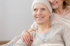 Cancer survivor lying in embrace. Happy cancer survivor with a headscarf, lying in an embrace of a close relative Stock Images