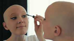 Happy cancer survivor woman putting on make up, looking in the mirror
