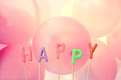 Happy candle letters with colourful balloons in the background Royalty Free Stock Image