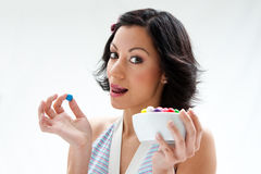 Happy candy girl. Happy beautiful candy girl with a bowl of colorful bubblegum candy balls licking her lip, isolated stock photography