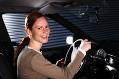 A Happy Car Driver at Night. A young female driver being happy and smiling behind the steering wheel in her car. This is a nighttime scene Stock Photo