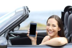 Happy car driver showing blank phone screen Stock Images