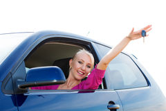 Happy car driver showing new car keys. Happy blonde car driver woman showing new car keys in car window Royalty Free Stock Images