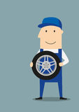 Happy car mechanic with wheel Stock Photos