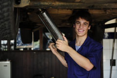 Happy car mechanic at work. Happy car mechanic working at the car repair shop royalty free stock photography