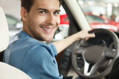 Happy car owner at the dealership. Handsome young men sitting at royalty free stock photos